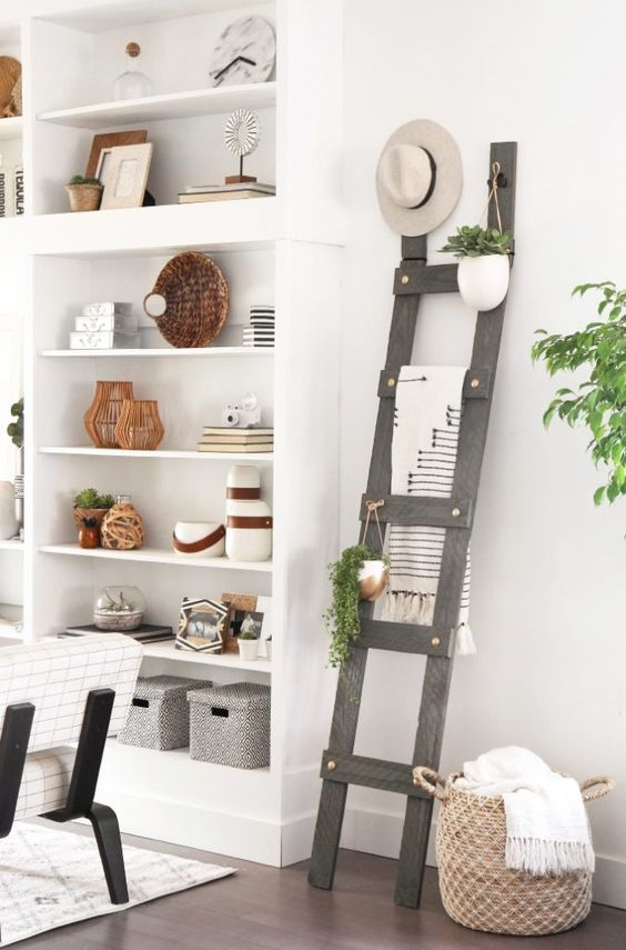 a grey ladder next to the shelving unit stores blankets, hanging greenery in pots and a hat on top