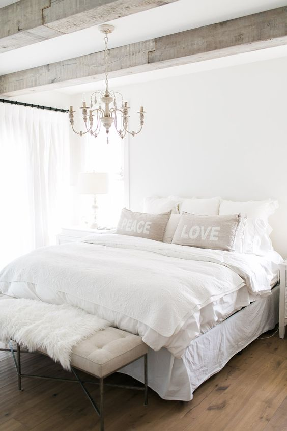 a neutral farmhouse bedroom with a chic white vintage chandelier that adds an elegant touch