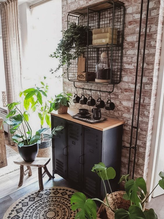 a black metal cabinet with a wooden top that softens it and a shelving unit on the wall for an industrial feel