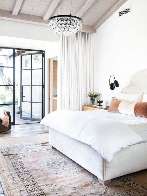 a fresh and modern bedroom with a small crystal chandelier for an elegant touch