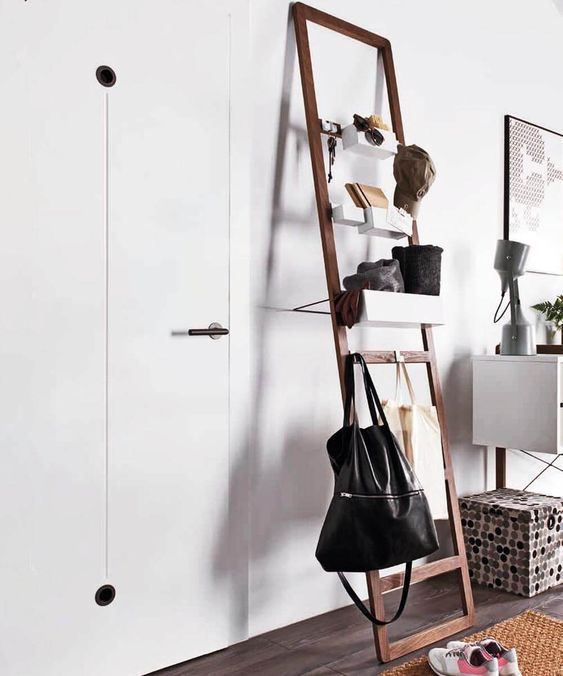 a modern ladder with bags on it and soem storage containers for small stuff is ideal for an entryway