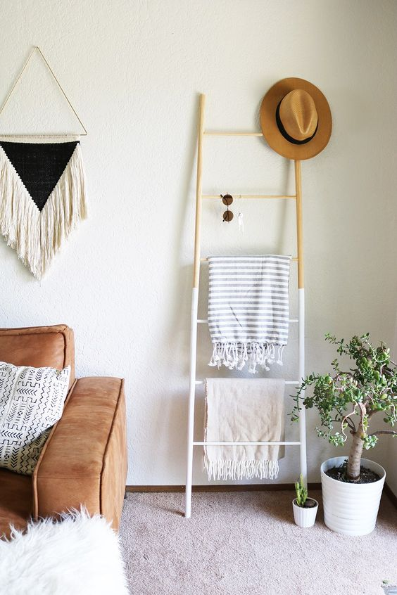 a small color block ladder with blankets, sunglasses and a hat doubles as a storage unit and as decor