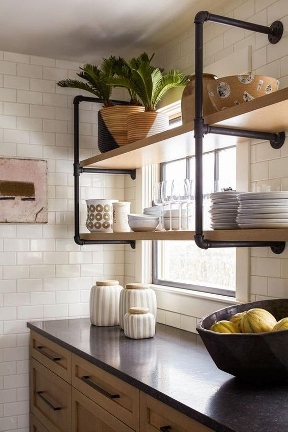 a wall-mounted shelving unit of black pipes and wood is a stylish idea for adding an industrial touch to the kitchen