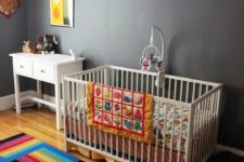 a bold nursery with grey walls but striped rugs, colorful buntings, colorful bedding and artworks for fun