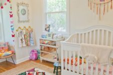 a bright and fun nursery with a colroful rug, bedding, an embroidery hoop with tassels and colorful butterflies