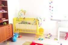 a bright and fun nursery with a printed rug, a yellow baby crib, colorful pompom garlands and bright toys
