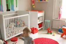 a bright and fun nursery with a whimsy artwork, colorful light garland, colorful rugs, toys and crochet baskets