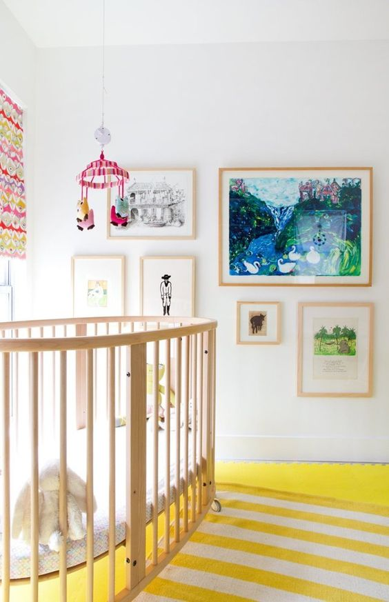 a bright and whimsy nursery with colorful layered rugs, bright artworks, a colorful mobile and curtains