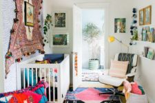 a bright boho nursery with a pompom rug on the wall, colorful rugs on the floor, pillows and bright bedding