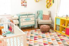 a bright mid-century modern nursery with a geometric rug, colorful bedding, a mobile, a bright changing table and yellow shelves