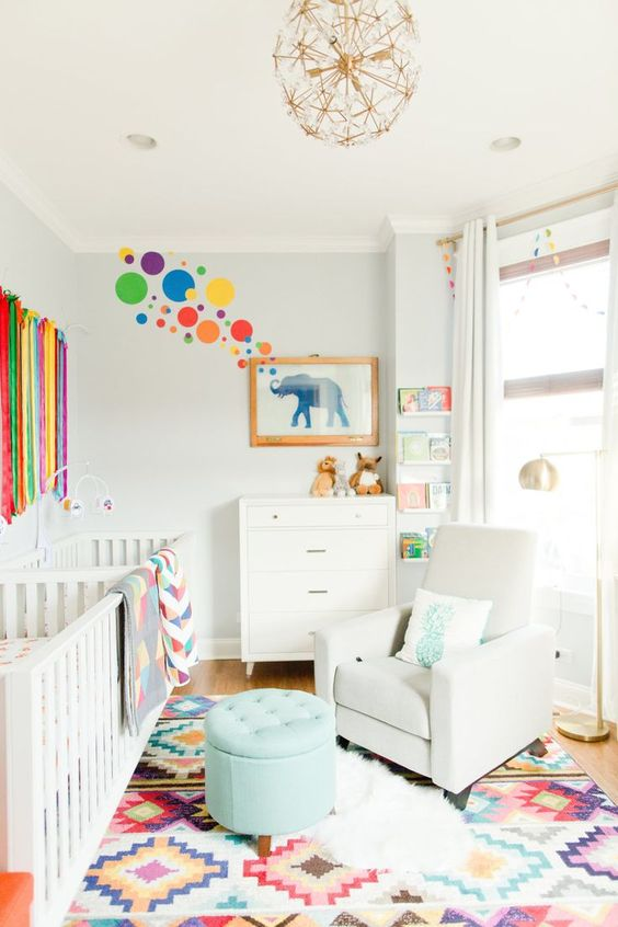 a bright modern nursery with a printed rug, a rainbow hanging, colorful bubbles and bright bedding