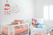 a bright nursery with a printed rug, colorful bedding and pillows, pompom garlands and fun and colorful toys