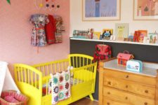 a bright nursery with a yellow bed, a quilted rug, colorful artworks and colorful books on the ledges
