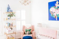 a brigth mixed pattern nursery with a floral rug, a navy ottoman, a brigth artwork and colorful books