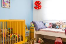 a brigth nrusery with a yellow crib, a printed rug, a marquee letter, bright toys and artworks for fun