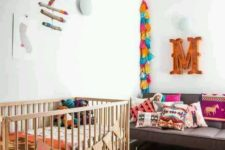 a colorful boho nursery with a bright rug, colorful tassel garlands, a mobile and bright textiles all over