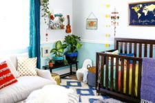 a colorful nursery with a printed rug, bright blue curtains, bedding and colorful pots and mobiles