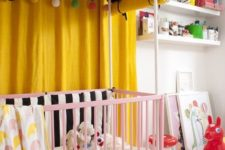 a colorful nursery with yellow curtains, a pink crib, a printed rug, colorful accessories and lots of toys