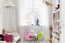 a fun nursery with colorful buntings, a bright striped rug and bedding plus colorful chairs by the table