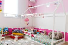 a fun nursery with pink walls, colorful bedding and a fun rug, colorful toys and artworks is amazing space