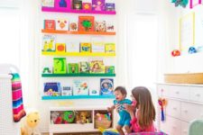 a super colorful nursery with rainbow shelves, a bright rug, bedding and colorful toys