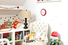 a tiny but super colorful nursery with bright bedidng, a colorful pompom rug, lots of bright toys, books and various accessories