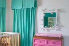 a whimsical nursery with turquoise curtains, a pink dresser, colorful watercolor ceiling and fun bedding