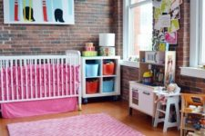 pink bedding, a pink rug, colorful artworks make this nursery with brick walls very whimsy and very bold