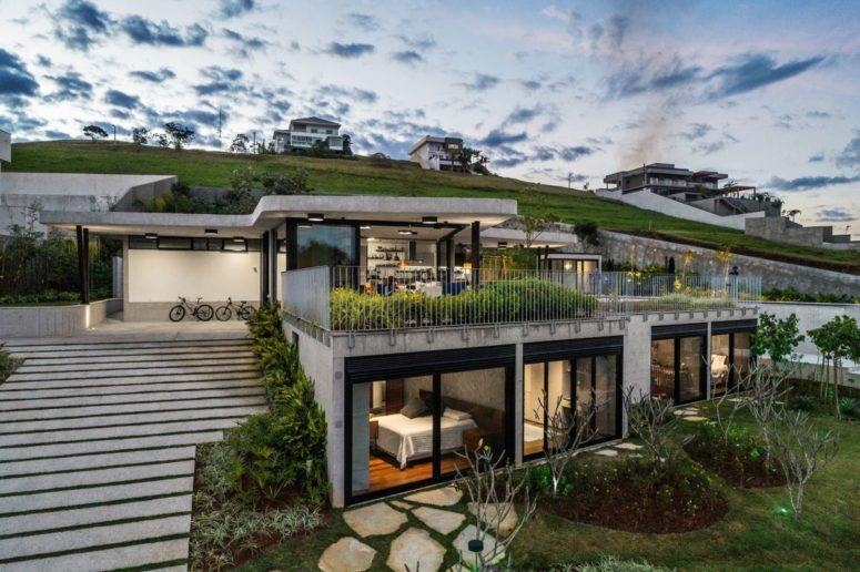This contemporary house is built into a steep slope and it takes all the advantages from it in the best way possible