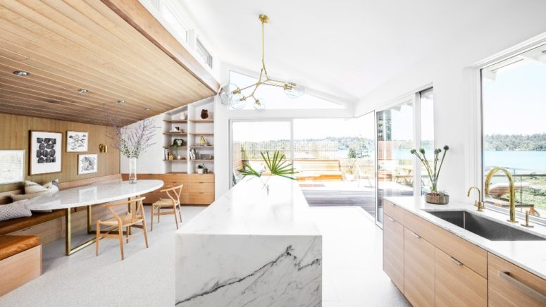 The kitchen and dining space are united into one layout, there's a large marble kitchen island, some sleek cabinets and a cozy dining nook