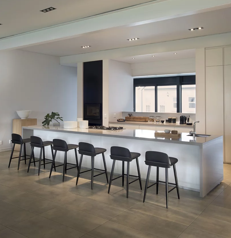 The kitchen is all white and sleek, with a giant kitchen island, a window to bring light in and black stools