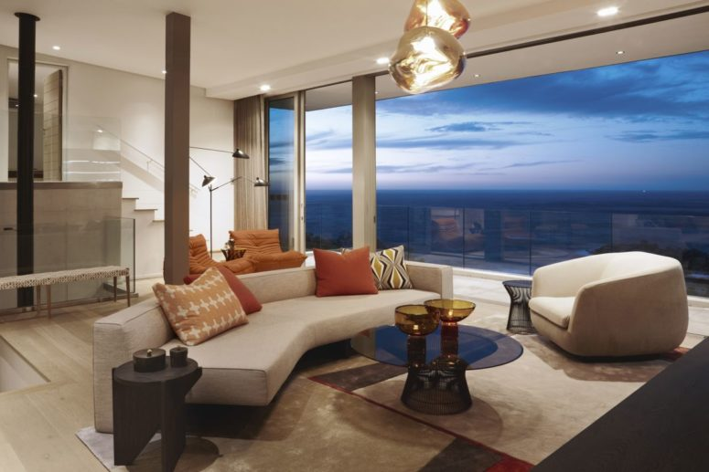The living room features gorgeous views, there is chic geometric furniture and catchy pendant lights
