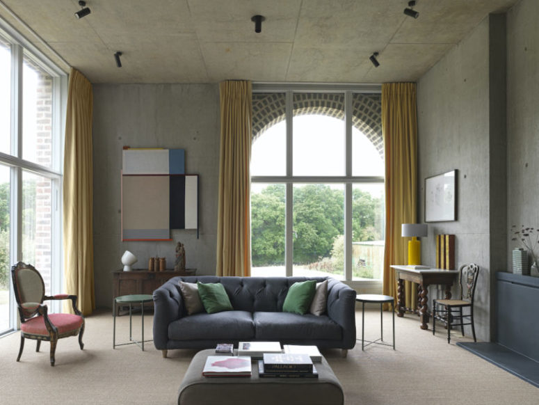 The living room is done with mustard curtains, a mix of refined and modern furniture in muted colors and bright artworks