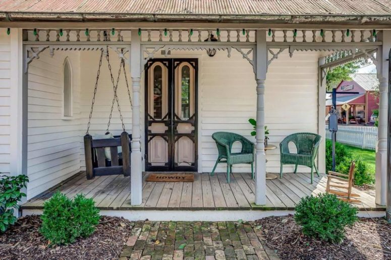 The porch features original black and pink doors, there's a hanging daybed and a green woven chair for a cozy feel