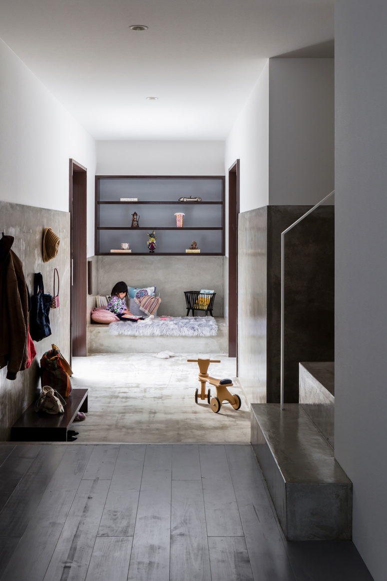 This is a small kid's nook done with built-in shelves, a concrete platform bed and two doors to outside
