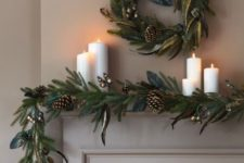 02 a chic evergreen garland with gilded touches, pinecones and a matching wreath over the mantel plus pillar candles