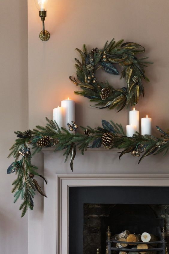 a chic evergreen garland with gilded touches, pinecones and a matching wreath over the mantel plus pillar candles