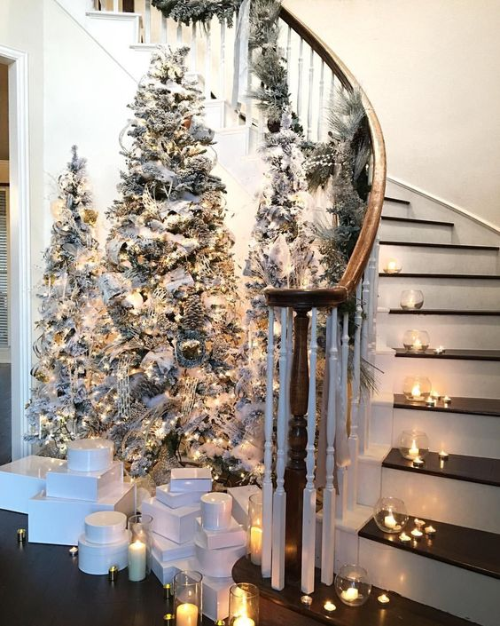 a chic winter fairy tale entryway with tree flocked Christmas trees, lights and neutral ornaments plus candles around