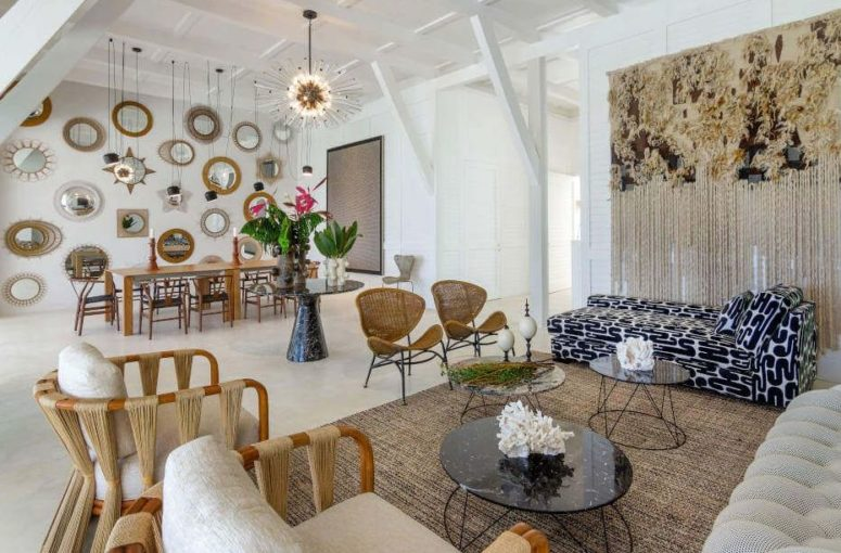 a quirky neutral layout with a living room and a dining space with eclectic decor, lots of mirrors and lamps and much texture