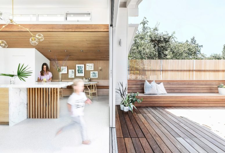 Glazed sliding doors allow entrance to the deck, which is clad with natural wood and indoors and outdoors are interconnected