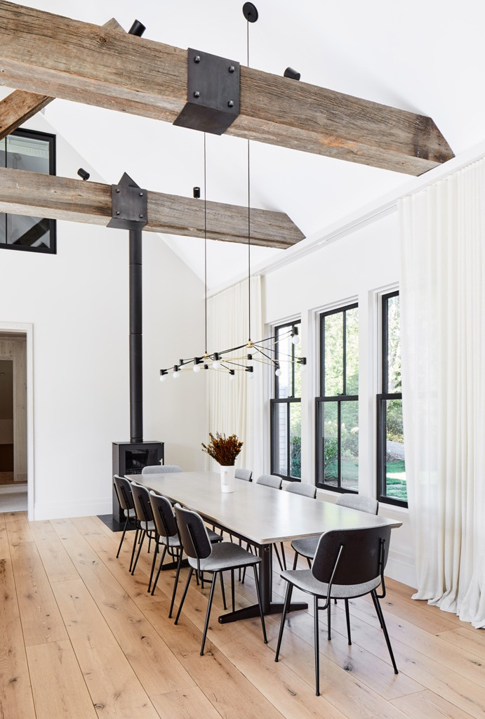 The dining space is done with a white table, grey chairs and a hearth