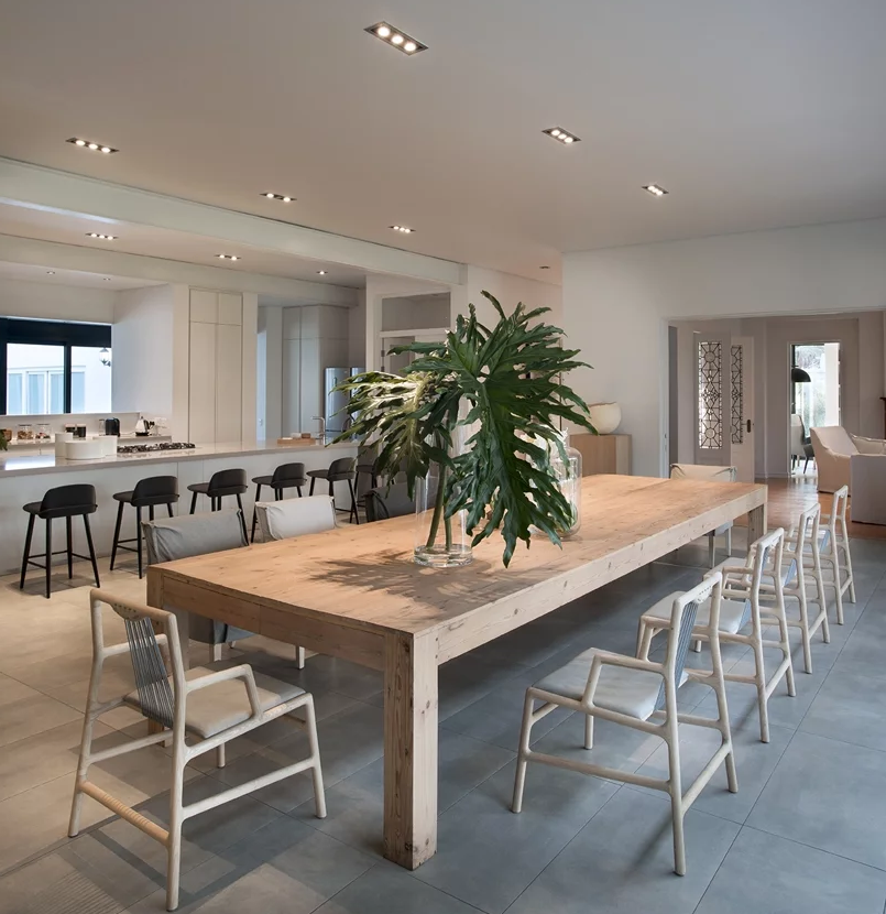 The dining space is done with a wooden dining set, a large table and comfy chairs