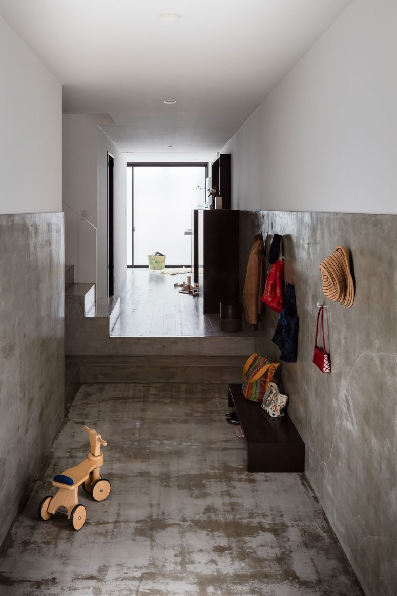 The entryway is done with concrete, a wooden bench and some hooks on the walls