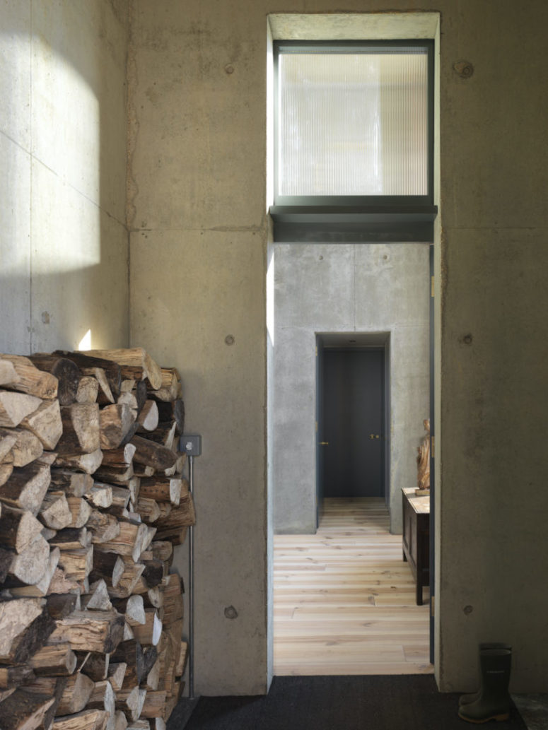 The house is done with raw concrete inside and wooden floors, and there's a firewood storage in the entrance