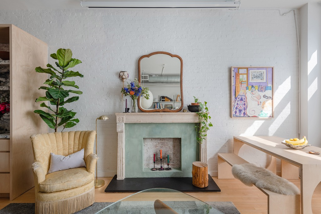 The living room is eclectic and shows off some vintage and refined furniture, decor and potted greenery plus muted colors