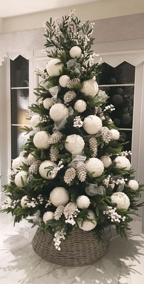 a bold Christmas tree with white berries, bleached pinecones and oversized white pompom ornaments for a cute look