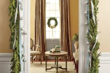 03 a greenery garland framing the doorway and some large bells hanging on ribbons for a chic and refined look