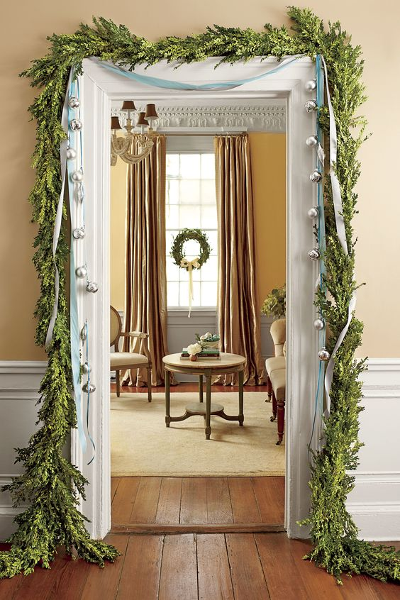 a greenery garland framing the doorway and some large bells hanging on ribbons for a chic and refined look