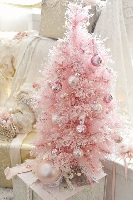 a pretty pink Christmas tree with shiny metallic ornaments that match in color and some pearly beads as decor