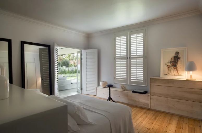 The bedroom is done in neutrals, with sleek furniture and large mirrors, it can be opened to outdoors